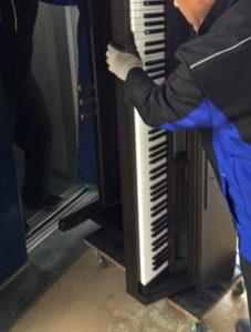 電子ピアノを立ててエレベータへ積み込む